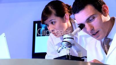 Arzt arbeitet am Mikroskop; Ärztin im Hintergrund