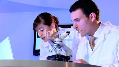 Ärztin und Arzt schauen abwechselnd durch ein Mikroskop