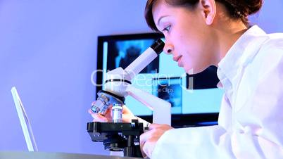 Ärztin arbeitet an Mikroskop und Computer