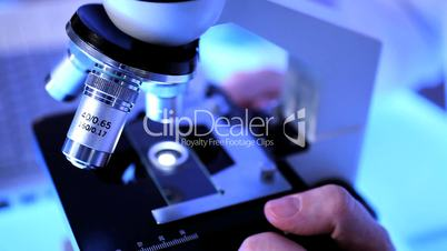 Nahaufnahme - Hand dreht an Mikroskop