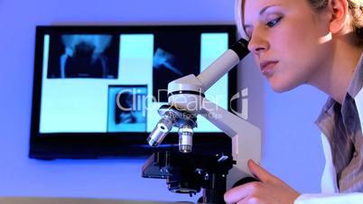 Blonde Ärztin schaut durch Mikroskop