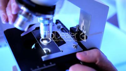 Nahaufnahme - Hand verstellt Mikroskop