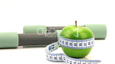 Zwei Hanteln mit grünem Apfel mit Maßband