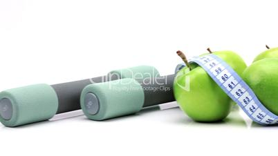 Zwei Hanteln mit grünen Äpfeln und Maßband