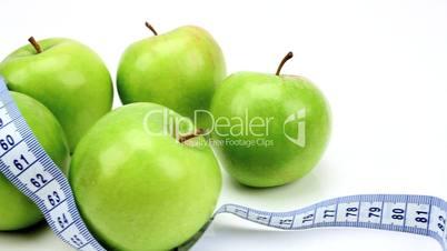Grüne Äpfel umschlungen von Maßband neben Hanteln