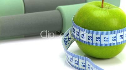 Grüner Apfel umschlungen von Maßband neben Hanteln
