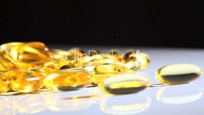 Gelbgolde Vitaminpillen - schwarzer Hintergrund