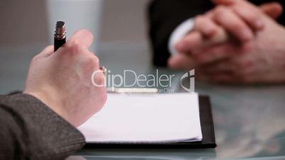 Hand schreibt auf Papier