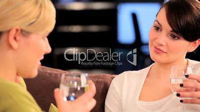 Braunhaarige Frau unterhält sich bei einem Glas Wasser