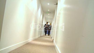 Mann und Frau gehen in einem Gang in einem Büro