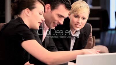 Besprechung - zwei Frauen mit Mann sitzend vor Laptop
