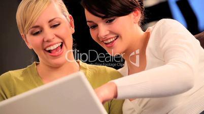 Zwei Frauen amüsieren sich vor einem Laptop