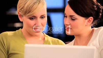 Zwei Frauen amüsieren sich an einem Laptop
