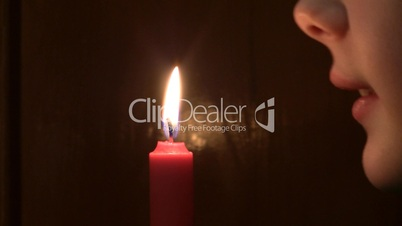 girl extinguishes a burning candle.