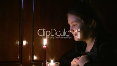 girl the teenager looks at a burning candle.