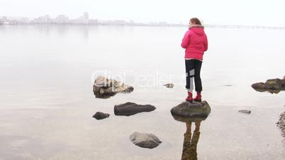 Girl throwing pebble in the water