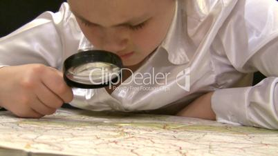 girl with magnifier studies a map of Europe.
