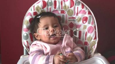 Baby girl sitting in high chair 1