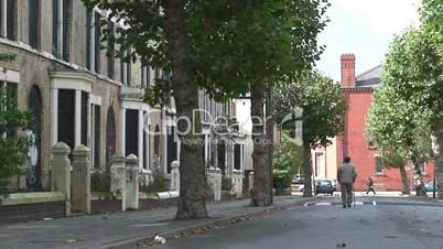 Old man walking past derelict houses