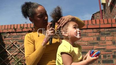 Young mother brushing her daughter's hair. 1