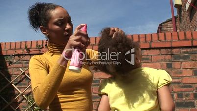 Young mother brushing her daughter's hair. 2