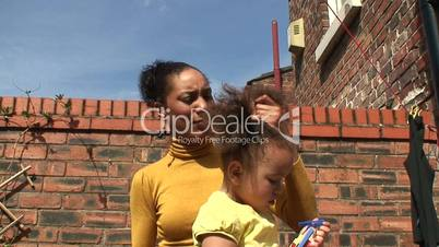 Young mother brushing her daughter's hair. 3