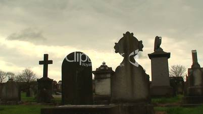 Hooded man walking among gravestones against a stormy sky