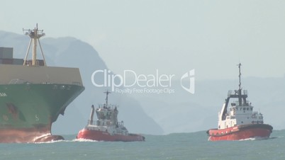 Tugs assist container ship in time lapse.