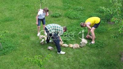 family carries stones for construction of flower bed.