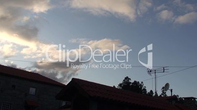 House roof with antennas at sunset time lapse