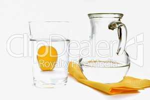 Wasser im Glaskrug neben Glas und Zitrone