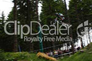 Sehr hoher und weiter Sprung eines Downhill Mountainbikers