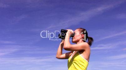Woman looking through binoculars against the blue sky