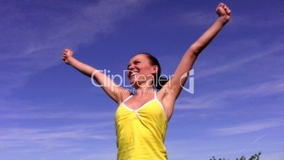 succesful woman jumping and throwing her hands in the air