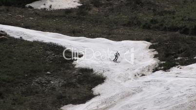 Skifahrer auf einer Piste mit wenig Schnee
