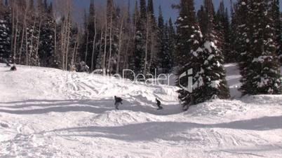 Drei Snowboarder fahren einen Hang herunter