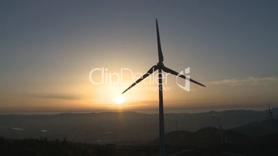Wind turbine in the mount at sunset