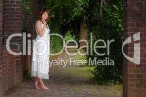 junge Frau in Arkaden barfuß stehend