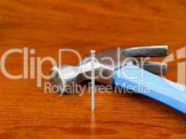 Hammer and nail on wooden background