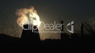 Chimney of power plant against sun