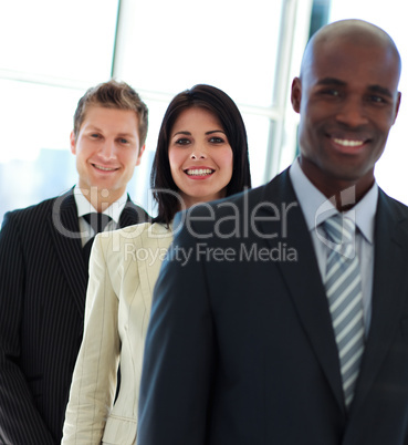 Smiling businesswoman in focus with her team in a row