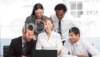 Multi-ethnic business people using a laptop in an office