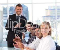 Businessman applauding with his team in a meeting