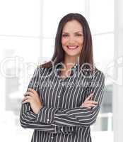 Smiling young businesswoman with folded arms
