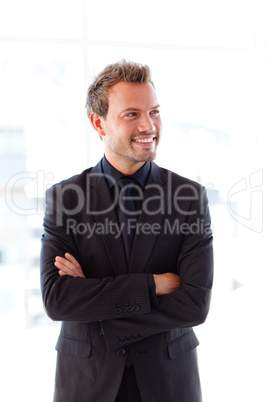 Smiling young businessman with folded arms