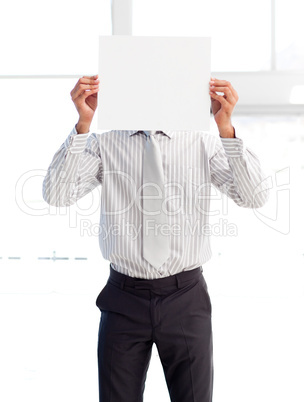 Businessman holding a white card covering his face