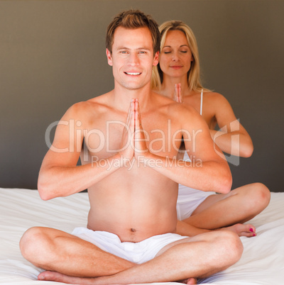 Young couple doing yoga on bed