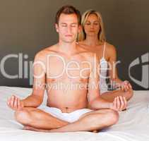 Portrait of a couple doing exercises on bed
