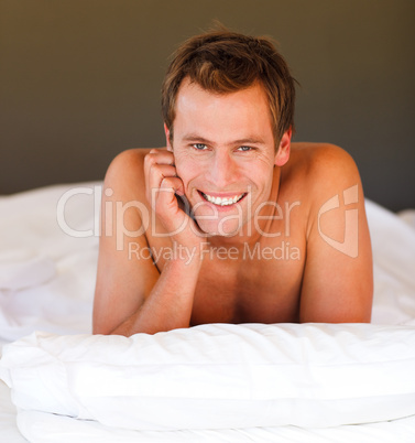 Attractive smiling youn boy in bed