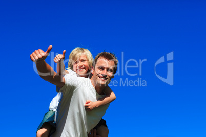 Son on father's back with thumbs up